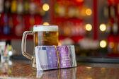Mug of beer and money — Stock Photo