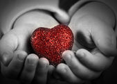 Red heart in the hands of a child — Stock Photo