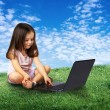 Stock Photo: Beautiful girl sitting with notebook on lawn