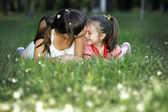 Cute mom and daughter relaxing on the lawn — Stock Photo