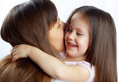 Little cute girl hugging her mother's neck — Stock Photo