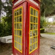 Cool red and yellow phone booth — Stock Photo