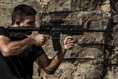 Menacing man pointing a machine gun — Stock Photo