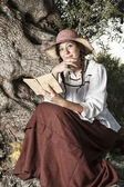 Beautiful girl in the countryside in the shade reading a book — Stock Photo