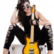 Beautiful girl in dark leather clothes holding an electric guitar — Stock Photo