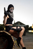 Beautiful girl with weapon and mask — Stock Photo