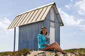 Beautiful girl in the beach next to a blue wood house — Stock Photo
