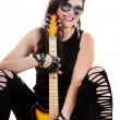 Beautiful girl in dark leather clothes holding an electric guitar — Stock Photo #19395171