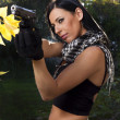 Beautiful girl with weapon - Stock Photo