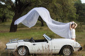 Beautiful woman posing on a white convertible car — Stockfoto
