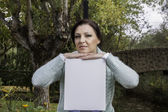 Young woman holding a blank canvas — Stockfoto