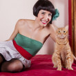 View of a pin-up girl happy with short hair in bed with a cute cat. — Stock Photo