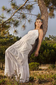 Young girl with a long white dress on the tree — Stock Photo