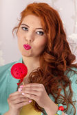Beautiful redhead girl with a lollipop candy — Stock Photo