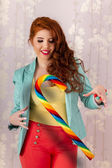 Beautiful redhead girl with a candy stick — Stock Photo