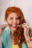 Beautiful redhead girl biting a candy stick — Stock Photo
