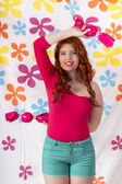 Beautiful redhead girl wearing colorful clothing holding giant candy — Stock Photo