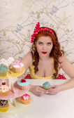 Beautiful pinup redhead girl with colorful cupcakes — Stock Photo