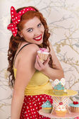 Beautiful pinup redhead girl holding a colorful cupcake — Stock Photo