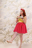 Beautiful pinup redhead girl holding a tray of colorful cupcakes — Stock Photo