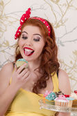 Beautiful pinup redhead girl holding a tray of colorful cupcakes — Photo