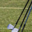 Golf clubs on a golf course field — Stock Photo #50804849