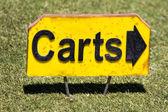 Гольф-поле зеленой травы с указывая знаком с буквами тележки — Стоковое фото