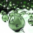 Foto Stock: Green christmas ornaments with star background