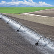 Farm field with irrigation system - Stock Photo