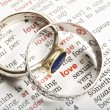 Wedding rings and the word love in dictionary - Stok fotoğraf