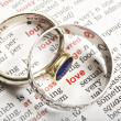 Wedding rings and the word love in dictionary - Stock fotografie