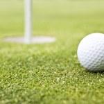 pelota de golf en un putting green con la bandera en el fondo — Foto de Stock