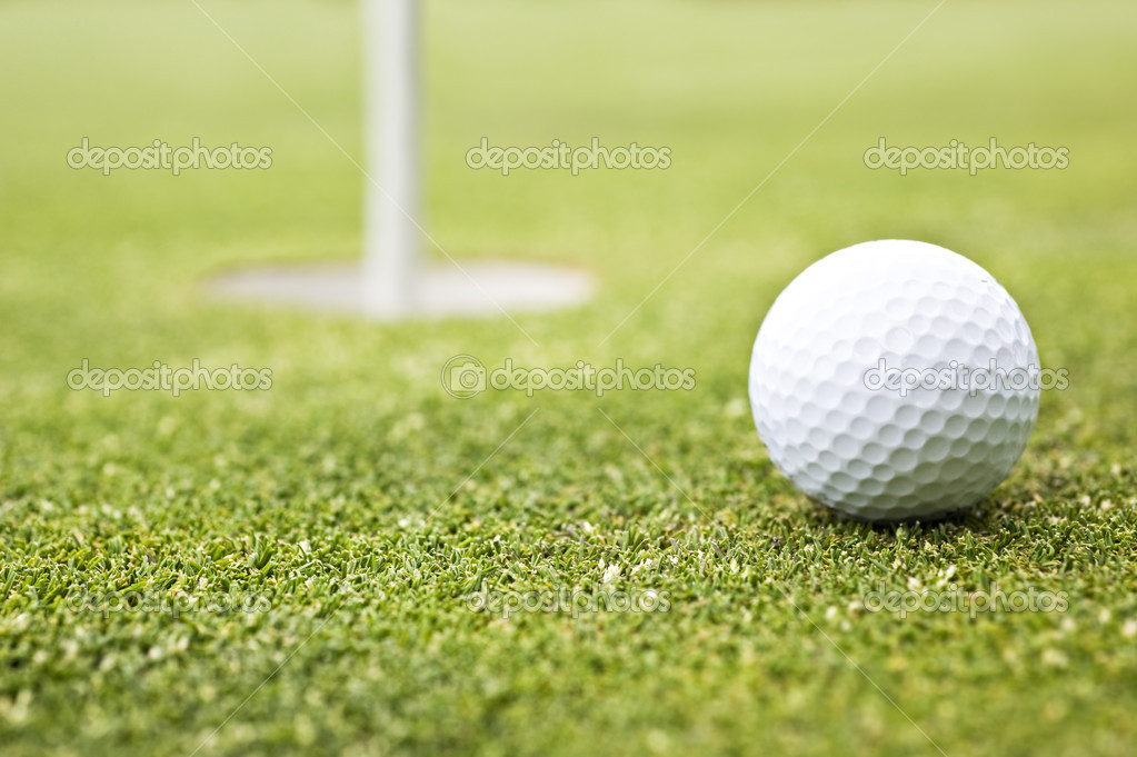 Golf ball on a putting green with the flag in the background - very shallow depth of field — Stock Photo #13612644