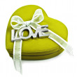 A Green heart with the word love spelled out in silver on  white - Stock Photo