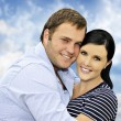 Beautiful happy  young couple with cloud background — Стоковая фотография
