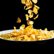 Crispy cornflakes  falling on white plate isolated on black back — Stock Photo