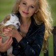 Beautiful blonde woman holding a puppy — Stock Photo #26820483
