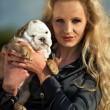 Beautiful blonde woman holding a puppy — Stock Photo #26820487
