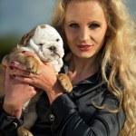 Beautiful blonde woman holding a puppy — Stock Photo