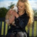 Beautiful blonde woman holding a puppy — Stock Photo #26820489