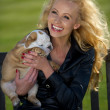 Beautiful blonde woman holding a puppy — Stock Photo