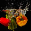 Stock Photo: Red, green and yellow bellpepper falling into water with splash on black background