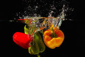Red, green and yellow bellpepper falling into the water with a splash on a black background — Stock Photo