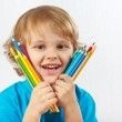 Little smiling boy holds color pencils on a white background — Stock Photo