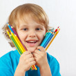 Stock Photo: Little smiling boy holds color pencils on a white background