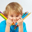Young cute blond boy holds color pencils on white background — Stock Photo #16044285