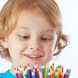 Little cute blond boy looks on color pencils on a white background — Stock Photo #16045029