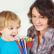 Foto Stock: Little smiling boy with his mother with color pencils on white background