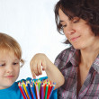 Little cute boy with his mother with color pencils on a white background — Stock Photo