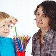 Little boy with young mother with color pencils on a white background — Stock fotografie